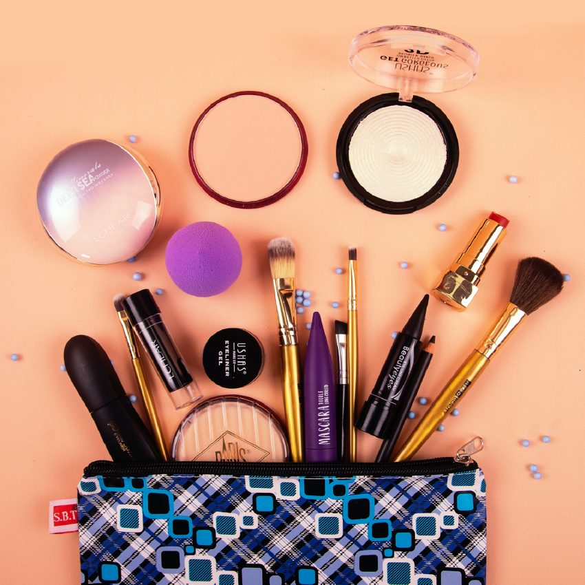 An open make-up bad with a ange of beauty products laying scattered out of the bag. Brushes, make-up sponges and blush.